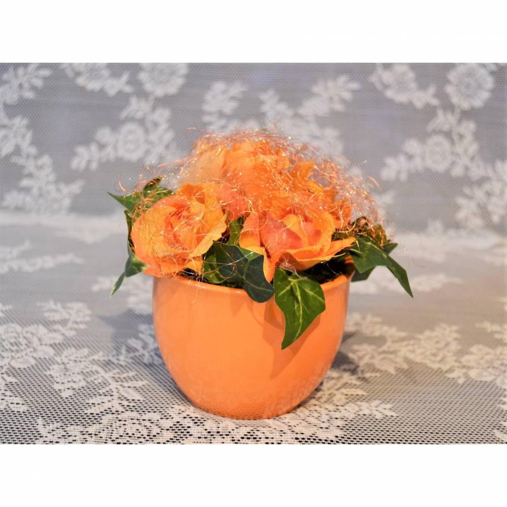 Gesteck in orange im Keramiktopf mit goldenem Feenhaar überzogen. Bild 1
