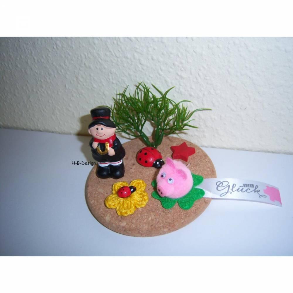 Glücksbringer oder auch Geldgeschenk-für das Neue Jahr, Glückssymbole auf einer Korkplatte dekoriert. Bild 1